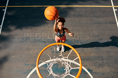 Buy stock photo High angle shot of a sporty young woman throwing a basketball into a net on a sports court