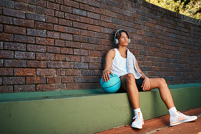 Buy stock photo Shot of a sporty young man taking a break after a game of basketball