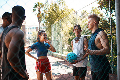 Buy stock photo Shot of a group of sporty young people chatting on a sports court