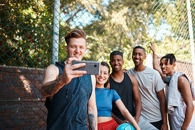 Buy stock photo Shot of a group of sporty young people taking selfies together outdoors