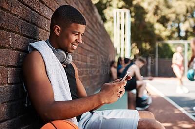 Buy stock photo Shot of a sporty young man using a cellphone while taking a break after a game of basketball