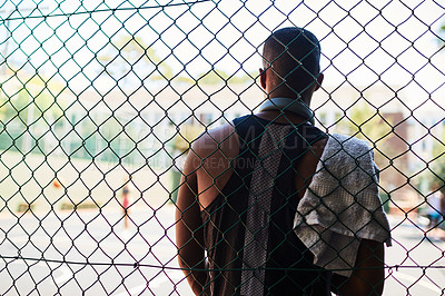 Buy stock photo Rearview shot of a sporty young man taking a break while standing against a fence on a sports court