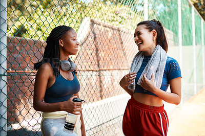 Buy stock photo Shot of two sporty young women chatting to each other against a fence outdoors