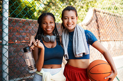 Buy stock photo Portrait of two sporty young women standing against a fence on a sports court