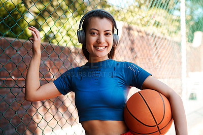 Buy stock photo Portrait of a sporty young woman holding a basketball while standing against a fence outdoors