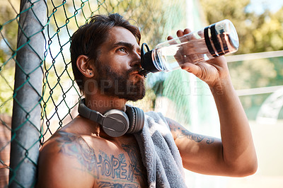 Buy stock photo Shot of a sporty young man drinking water while standing against a fence outdoors