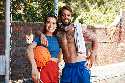Buy stock photo Portrait of two sporty young people standing against a fence on a sports court