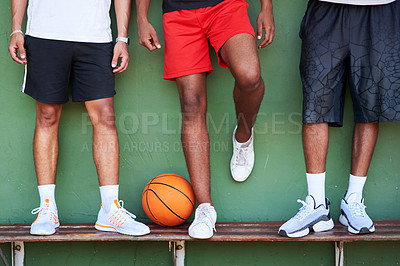 Buy stock photo Closeup shot of a group of sporty men standing on a bench alongside a basketball against a wall