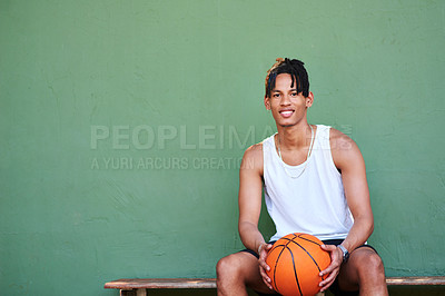 Buy stock photo Portrait of a sporty young man holding a basketball while sitting on a bench against a wall