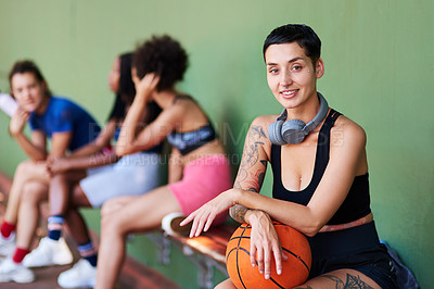 Buy stock photo Portrait of a sporty young woman taking a break with her friends after a game of basketball