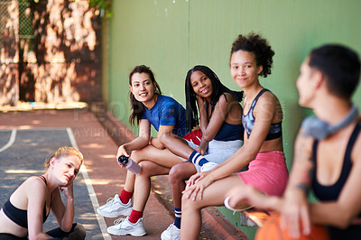 Buy stock photo Shot of a group of sporty young women chatting to each other on a sports court