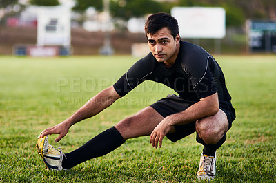 Buy stock photo Full length shot of a handsome young sportsman stretching alone before a rugby practice during the day