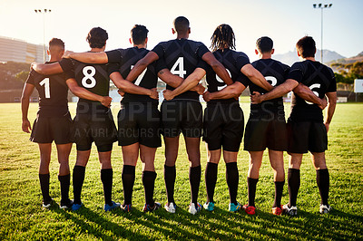 Buy stock photo Full length shot of a unrecognizable group of sportsmen standing together with their arms around each other before playing rugby