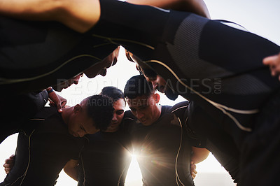 Buy stock photo Low angle shot of a diverse group of sportsmen huddled together before playing a game of rugby