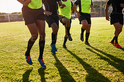 Buy stock photo Cropped shot of an unrecognizable group of sportsmen warming up before playing rugby during the day