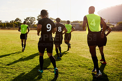 Buy stock photo Full length shot of an unrecognizable group of sportsmen warming up before playing rugby during the day
