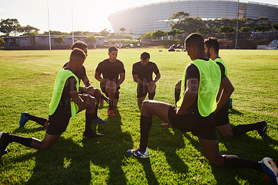 Buy stock photo Full length shot of a diverse group of sportsmen stretching before a rugby practice during the day