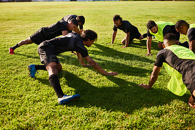 Buy stock photo Cropped shot of a diverse group of sportsmen stretching before a rugby practice during the day