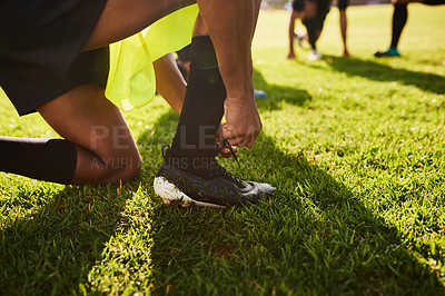 Buy stock photo Cropped shot of an unrecognizable young sportsman tying his shoelaces before playing rugby during the day