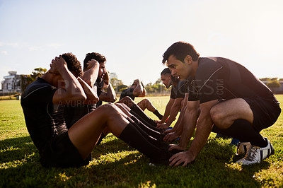 Buy stock photo Full length shot of a diverse group of sportsmen training during a rugby practice in a sports club