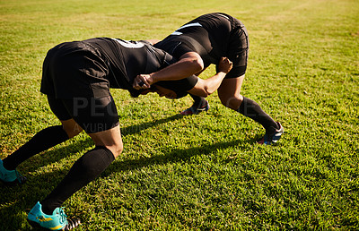 Buy stock photo Full length shot of two unrecognizable sportsmen tacking each other during a rugby game during the day