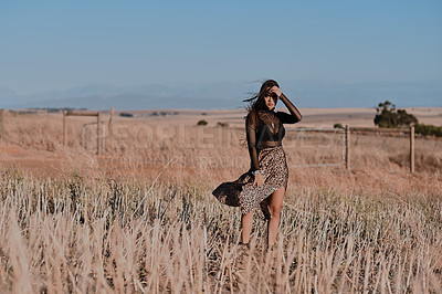 Buy stock photo Full length portrait of an attractive young woman standing alone and posing in a meadow during the day