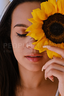Buy stock photo Shot of a beautiful young woman holding a sunflower in front of her face