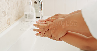 Buy stock photo Cropped shot an unrecognizable woman helping her young son wash his hands in the bathroom at home
