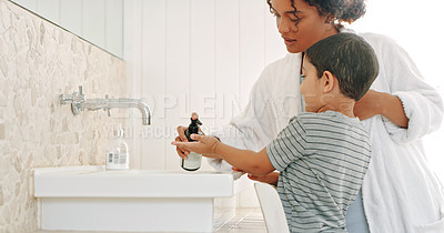 Buy stock photo Cropped shot a mother helping her adorable young son wash his hands in the bathroom at home