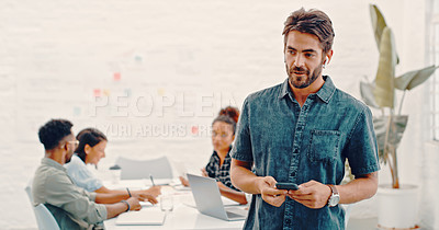 Buy stock photo Shot of a young businessman using a smartphone while his colleagues have a meeting in the background