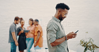 Buy stock photo Shot a businessman using his cellphone while colleagues stand in the background