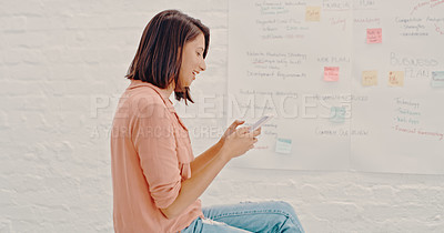 Buy stock photo Cropped shot of a young businesswoman using her cellphone while sitting in her office