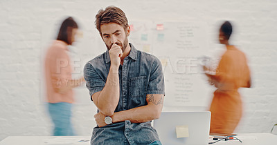 Buy stock photo Cropped shot of a businessman standing alone while his colleagues work together in the background