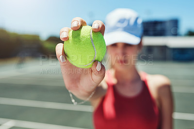 Buy stock photo Cropped shot of an unrecognizable sportswoman standing alone and holding a tennis ball during a training session
