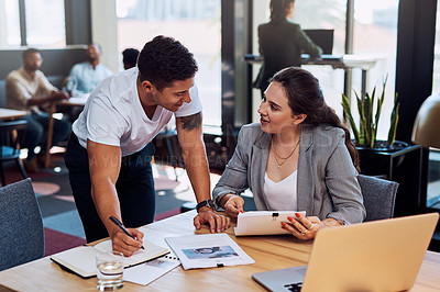 Buy stock photo Shot of two businesspeople going through paperwork together in an office