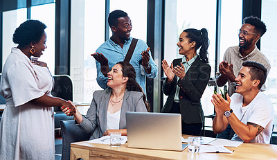 Buy stock photo Shot of a group of businesspeople applauding their colleagues in an office