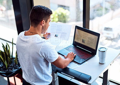 Buy stock photo Shot of a young businessman going through paperwork and working on a laptop while walking on a treadmill in an office