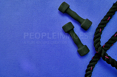 Buy stock photo High angle shot of two lightweight dumbbells and piece of rope placed on a blue background inside of a studio