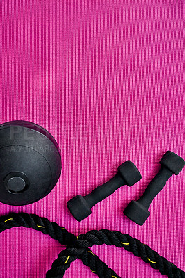 Buy stock photo High angle shot of two lightweight dumbbells and piece of rope placed on a pink background inside of a studio
