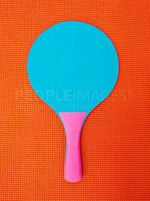 Buy stock photo High angle shot of a table tennis bat placed on top of an orange background inside of a studio
