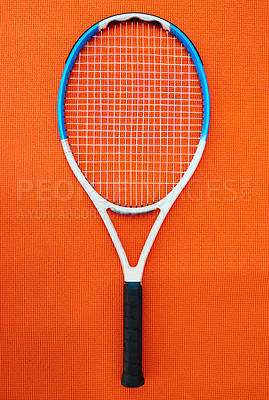 Buy stock photo High angle shot of a single tennis racket placed on an orange background inside of a studio