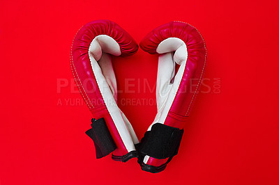 Buy stock photo High angle shot of a pair of boxing gloves placed together on top of a red background inside of a studio