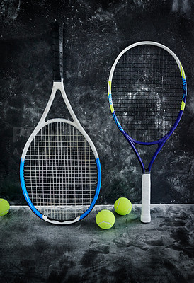 Buy stock photo Studio shot of tennis essentials placed against a dark background inside of a studio
