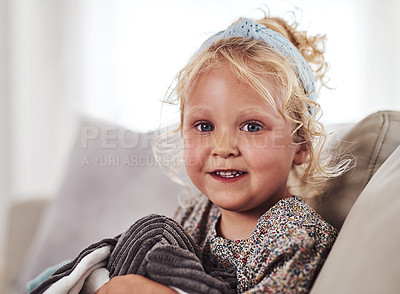 Buy stock photo Cropped portrait of an adorable little girl sitting alone on the sofa and playing with her toys at home