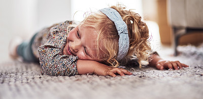 Buy stock photo Cropped shot of an adorable little girl lying alone on the living room floor at home