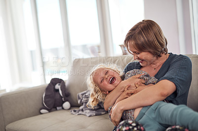 Buy stock photo Cropped shot of an attractive young mother sitting on the sofa and hugging her daughter at home