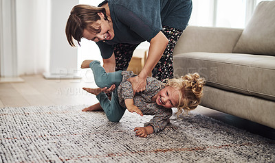 Buy stock photo Cropped shot of an attractive young mother and playing with her daughter in the living room at home