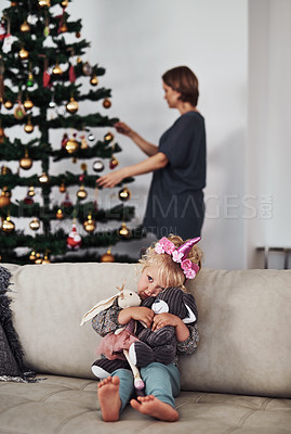 Buy stock photo Cropped shot of an adorable little girl sitting on the sofa while her mother fixes the Christmas tree behind her