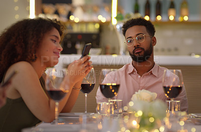 Buy stock photo Cropped shot of a handsome young man looking bored while his friends use their cellphones at the dinner table