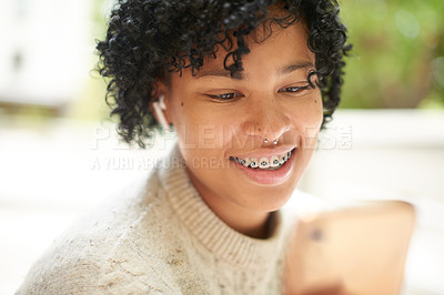 Buy stock photo Shot of a student using a cellphone while wearing wireless earphones at campus